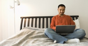 Young Man in Bed Using Laptop
